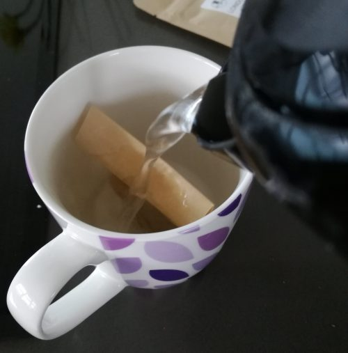Kettle puring boiling water into mug