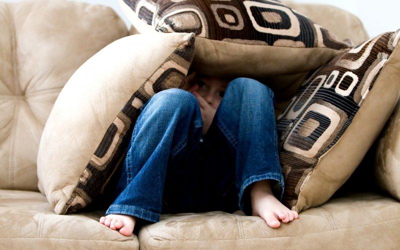 Woman hiding on sofa under a pile of cushions
