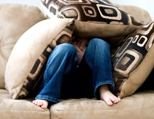 Woman hiding on sofa under a pile of cushions