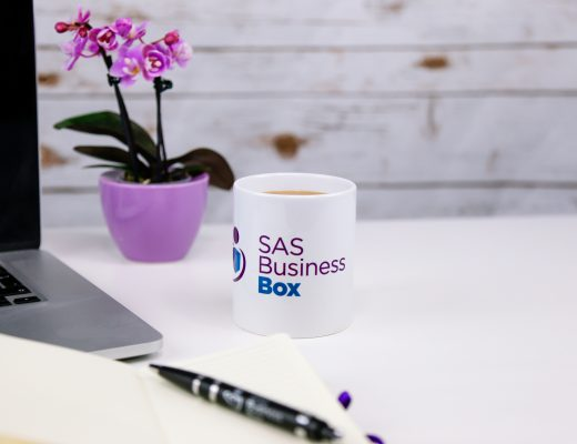 Mug with SAS business box logo next to pen and laptop