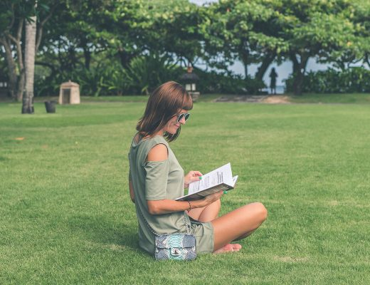Woman reading book whilst sitting outside on grass