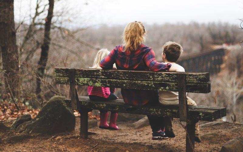 Woman sitting on bench with two children