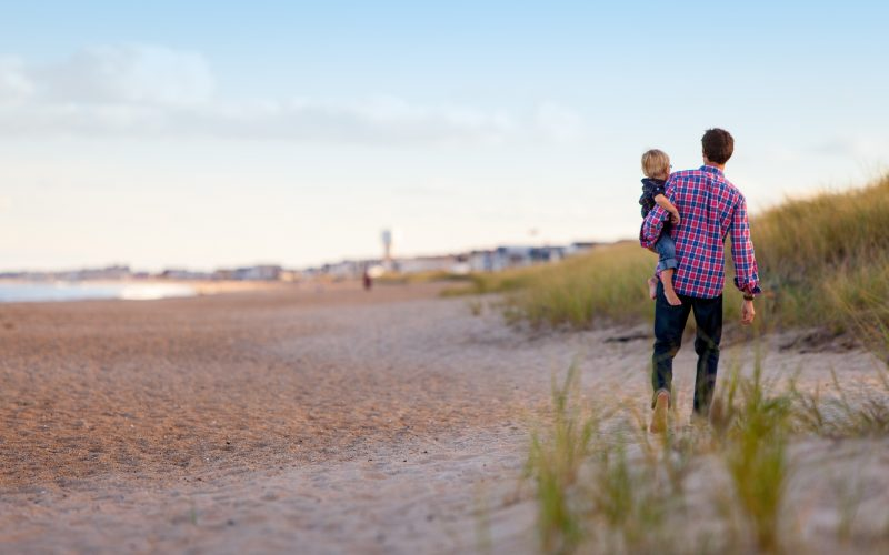 Man carrying toddler on the beach