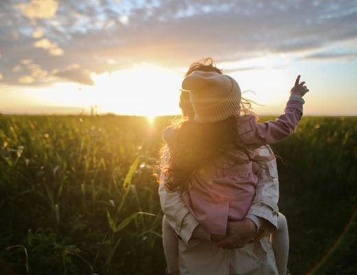 Adult holding child with sunset in background