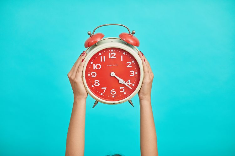 Hands holding up red alarm clock