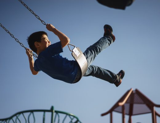 Young boy swinging on fairground ride