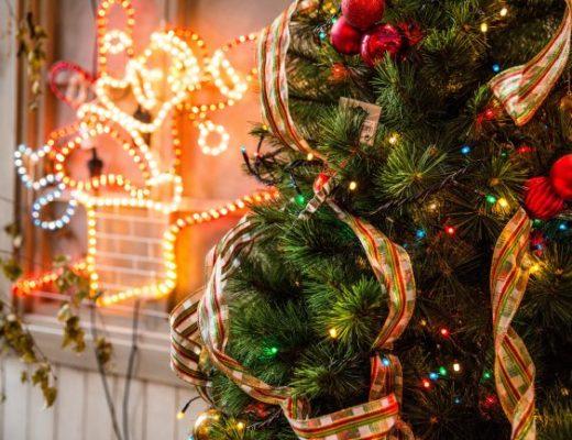 Christmas tree with decorations next to neon Santa light