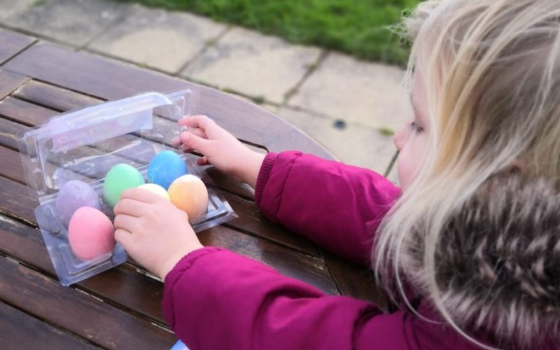 Girl drawing with egg shaped chalk crayons