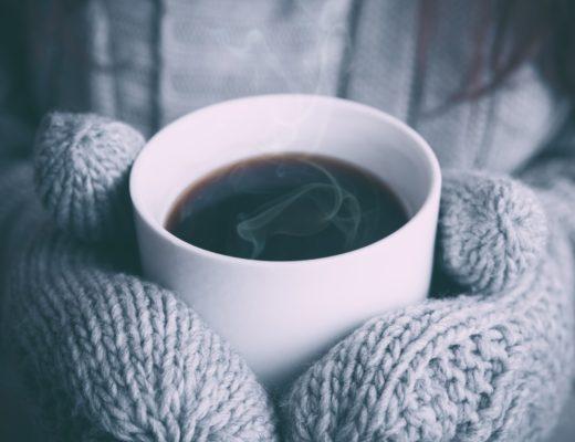 Gloved hands holding mug of hot liquid