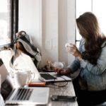 Woman sitting at laptop with mug