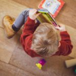 Toddler child looking at books