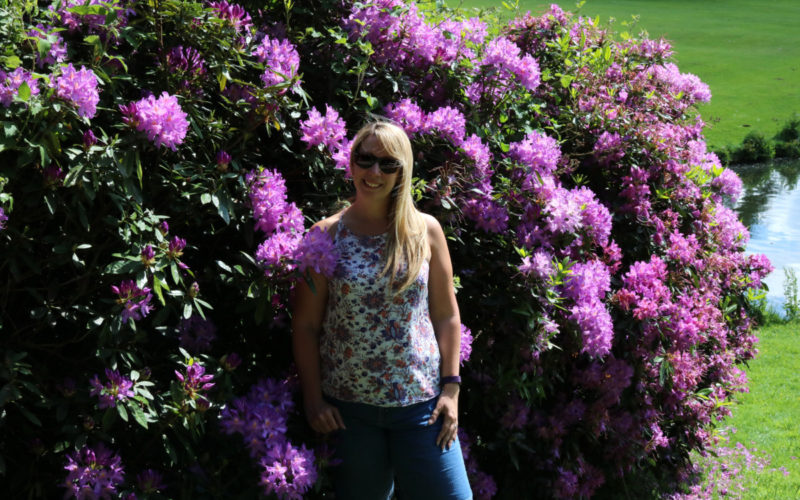 Woman standing by large purple flowering bush